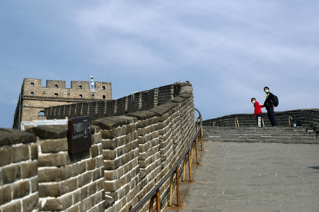 A man and a child wearing protective face masks look back as they walk on the Badaling Great Wall of China after it reopened for business following th...