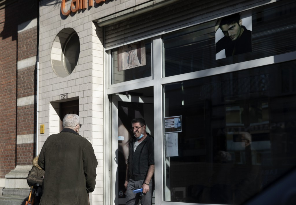 A barber wearing a mouth mask speaks with a client outside his shop in Antwerp, Belgium, Monday, March 23, 2020. After Belgian Prime Minister Sophie W...