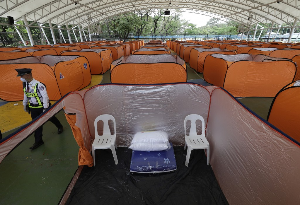 A security guard wearing a protective mask walks beside isolation tents that will serve as a quarantine facility for people showing symptoms of the CO...