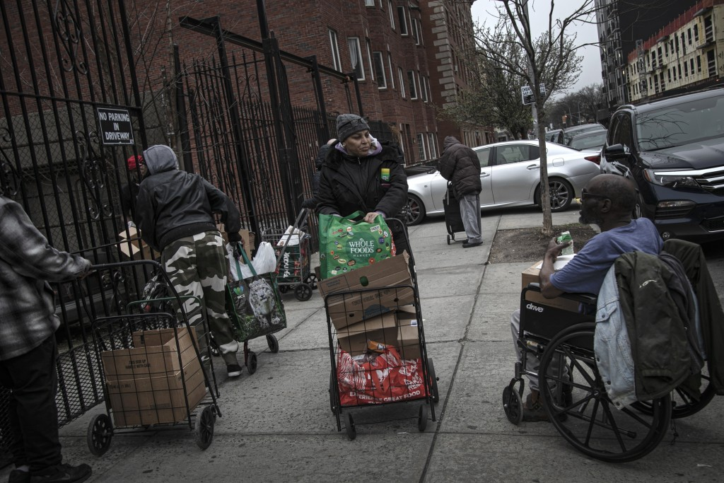 Elizabeth Pantojas 52, center, pushes her cart of food donations from St. Stephen Outreach in the Brooklyn borough of New York, on Friday, March 20, 2...