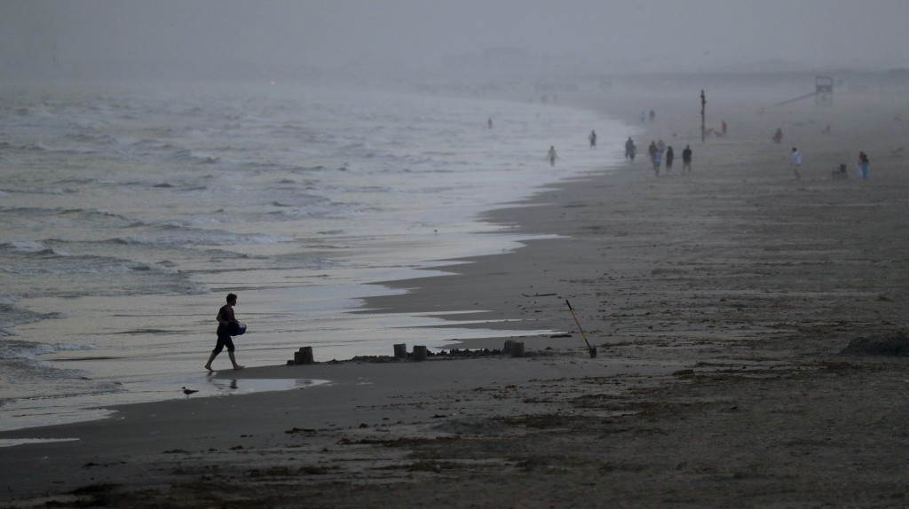Beach goers are scattered along the water front, March 22, 2020, in Port Aransas, Texas. Officials have strongly discouraged large gatherings of sprin...