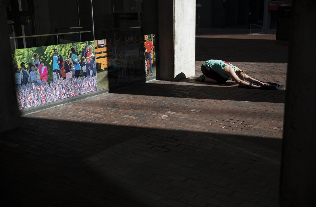 Unable to work out at her gym since it closed due to coronavirus, a woman stretches in a quiet corner while exercising at the entrance to City Hall, M...