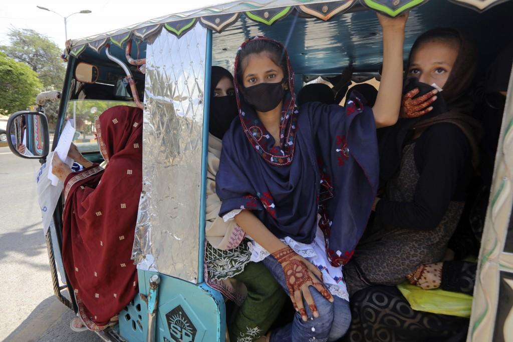 People traveling in a motorized rickshaw wear face masks in an effort to avoid the spread of the coronavirus, in Karachi, Pakistan, Tuesday, March 24,...