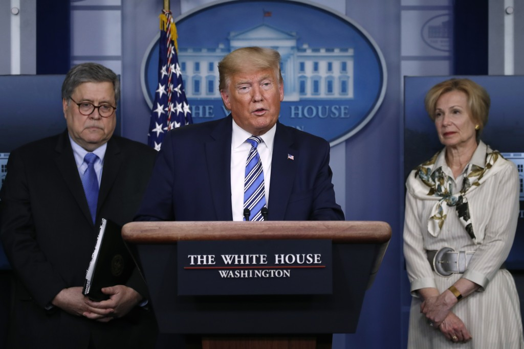 President Donald Trump speaks about the coronavirus in the James Brady Briefing Room, Monday, March 23, 2020, in Washington, as Attorney General Willi...