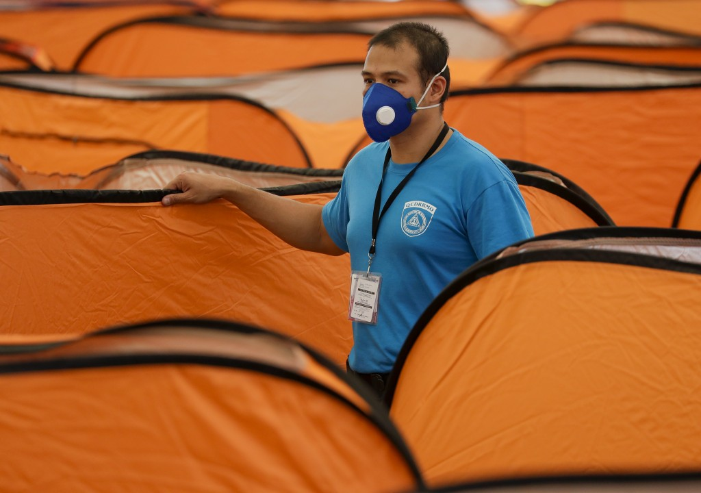 A worker from the city emergency response team checks isolation tents at a basketball court inside the Quezon Memorial Circle that will serve as a qua...
