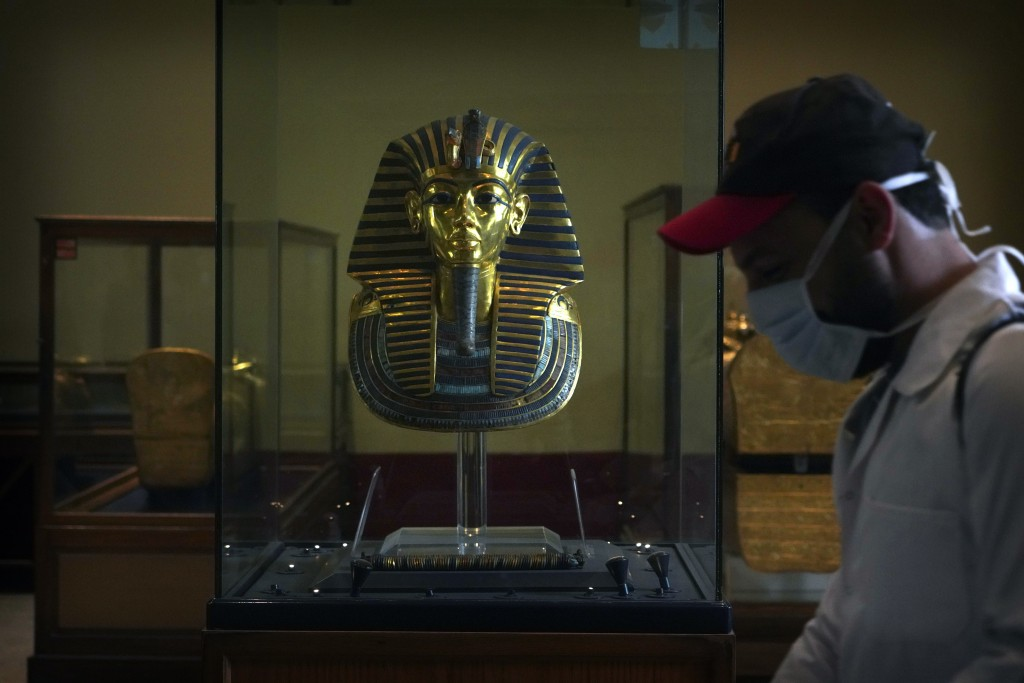 A worker disinfects around King Tut's famous mask in the Egyptian Museum in an effort to help prevent the spread of the coronavirus, in Tahrir Square,...