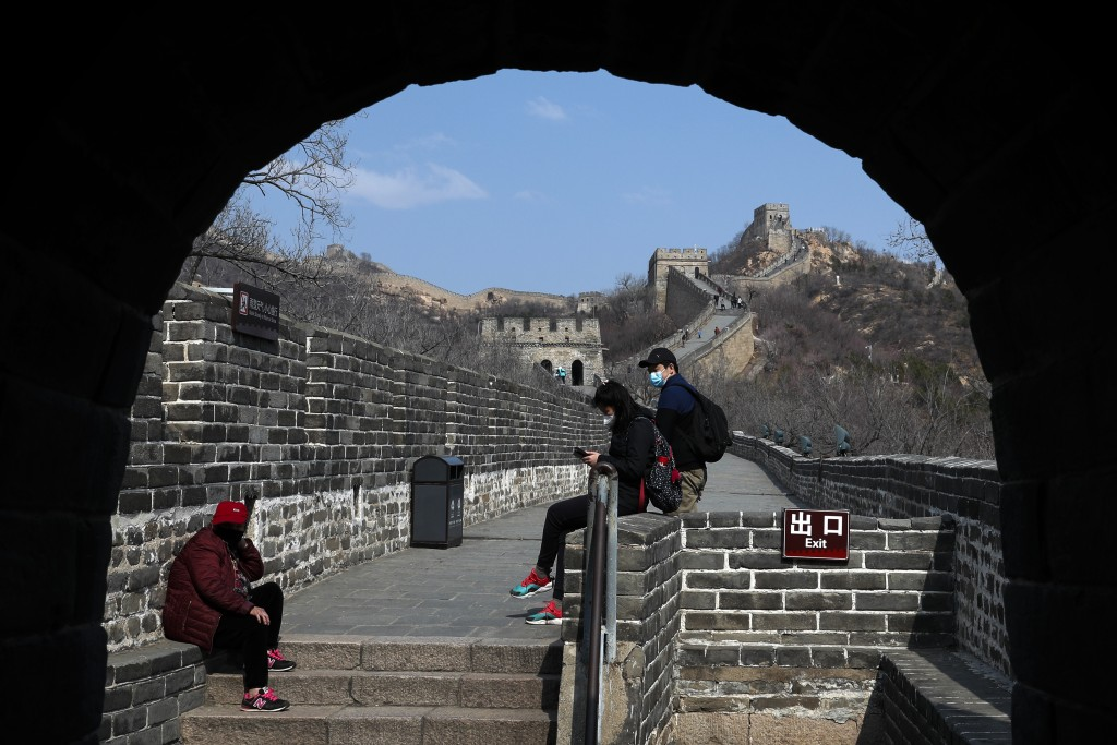 Visitors wearing protective face masks take a rest as they visit the Badaling Great Wall of China after it reopened for business following the new cor...