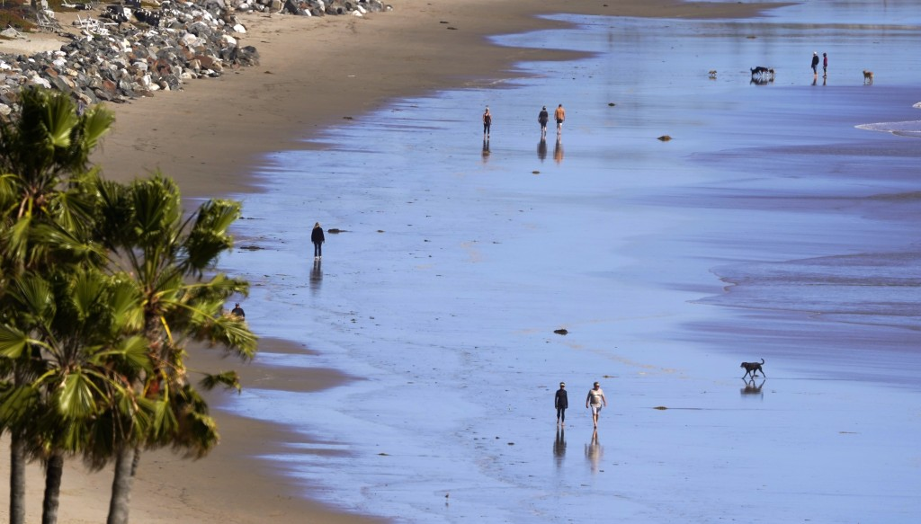 People walks along Zuma Beach, Monday, March 23, 2020, in Malibu, Calif. Officials are trying to dissuade people from using the beaches after Californ...