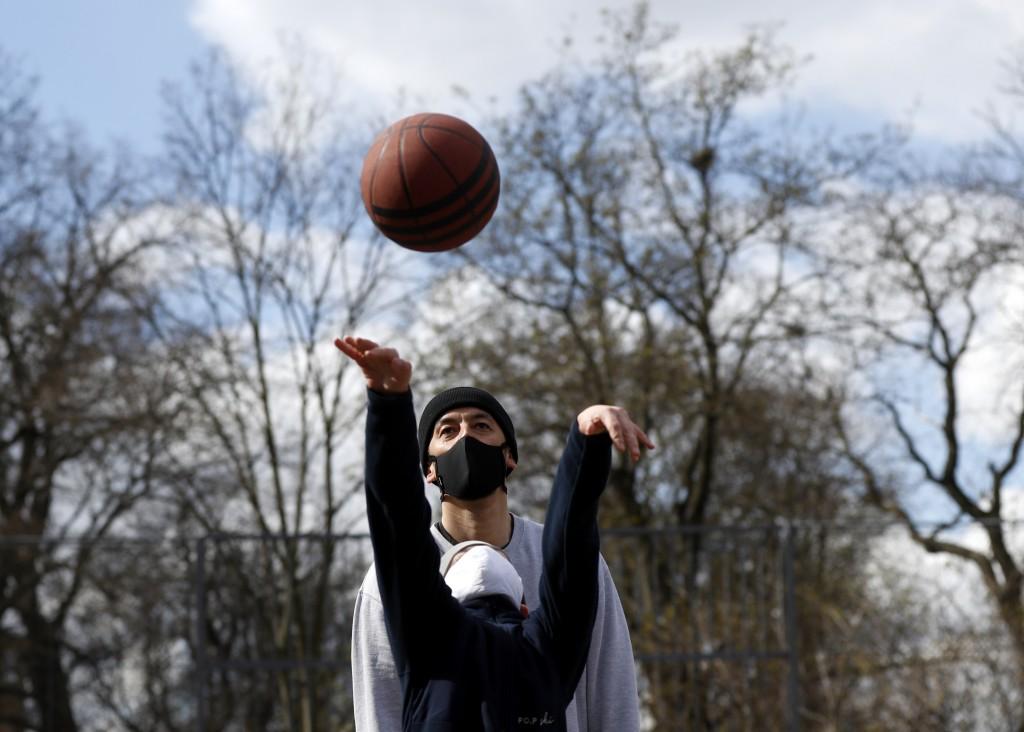 A man watches his son throw a ball as they play basketball in a park in Prague, Czech Republic, March 22, 2020. (AP Photo/Petr David Josek)