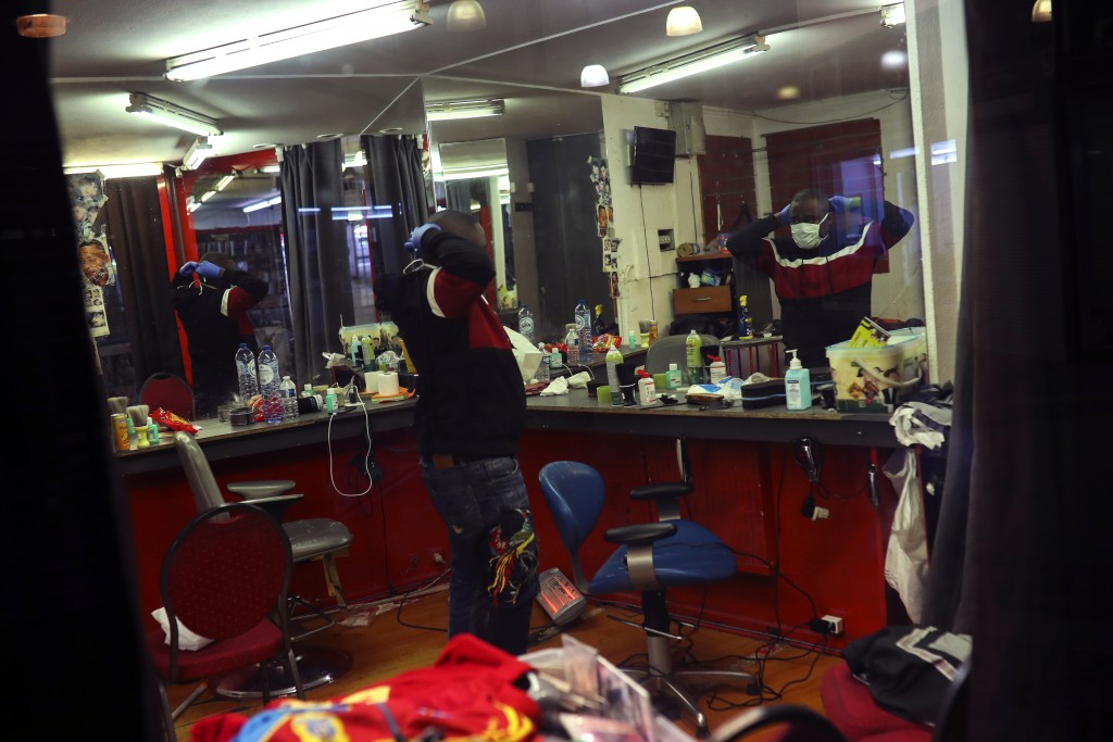 A hairdresser puts on his protective mask in front of a mirror prior to cutting a client's hair at a hair salon in the Matonge Quarter of Brussels, Mo...