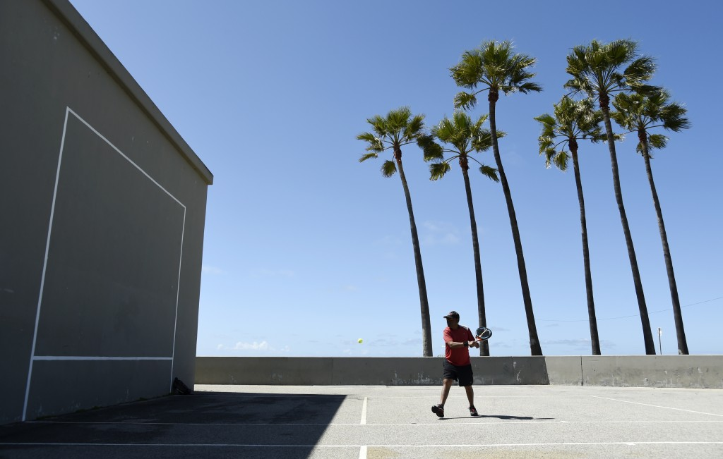 Lemmon McMillan of Playa del Rey, Calif., plays racquetball on the Venice Beach Boardwalk, March 23, 2020, in Los Angeles. (AP Photo/Chris Pizzello)