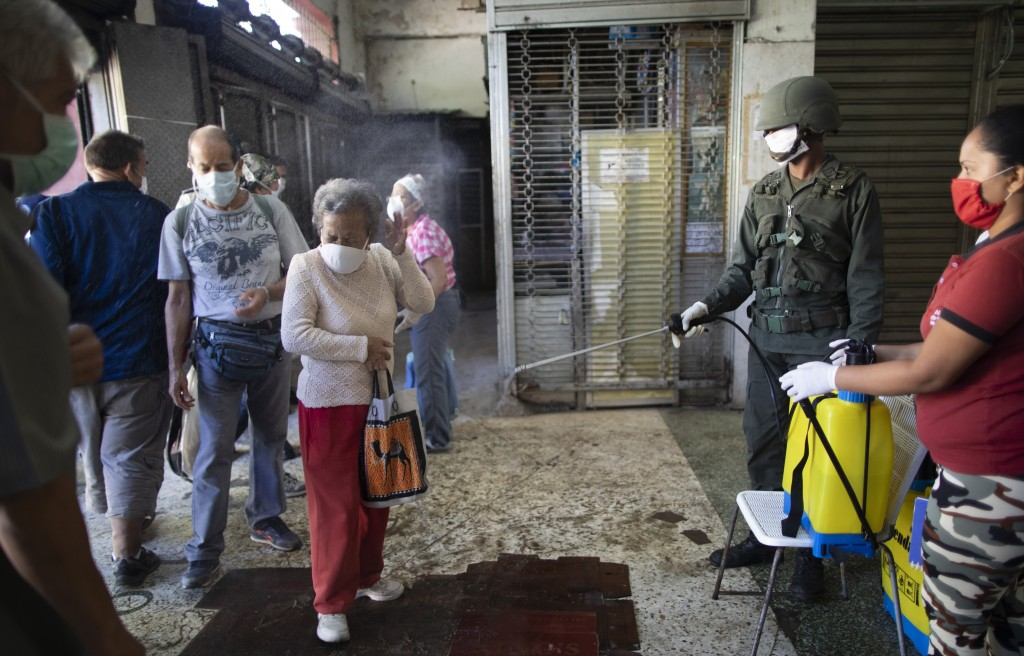 An elderly woman, wearing a protective face mask is sprayed with a disinfectant bleach solution by a soldier as a preventive measure against the sprea...