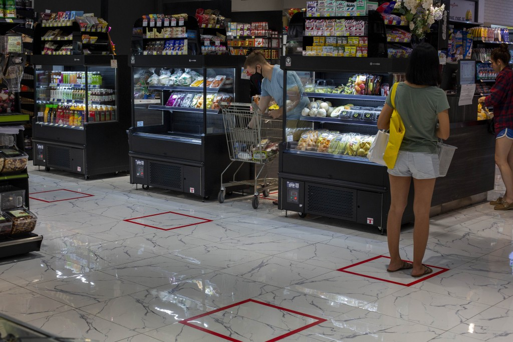 Customers stand in an area marked to prompt social distancing leading to cashers at a supermarket in Bangkok, Thailand, Tuesday, March 24, 2020. Most ...