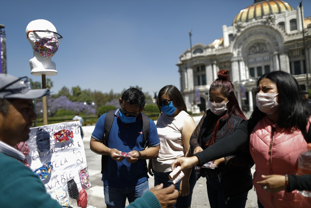 Customers purchase homemade fabric face masks being sold for 20 pesos (around 85 cents) from Jorge Rodriquez, on a street in Mexico City, Monday, Marc...