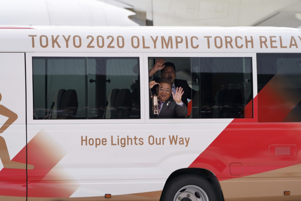 FILE - In this March 20, 2020, file photo, Japanese comedians Mikio Date, foreground, and Takeshi Tomizawa leave with the Olympic flame during the Fla...