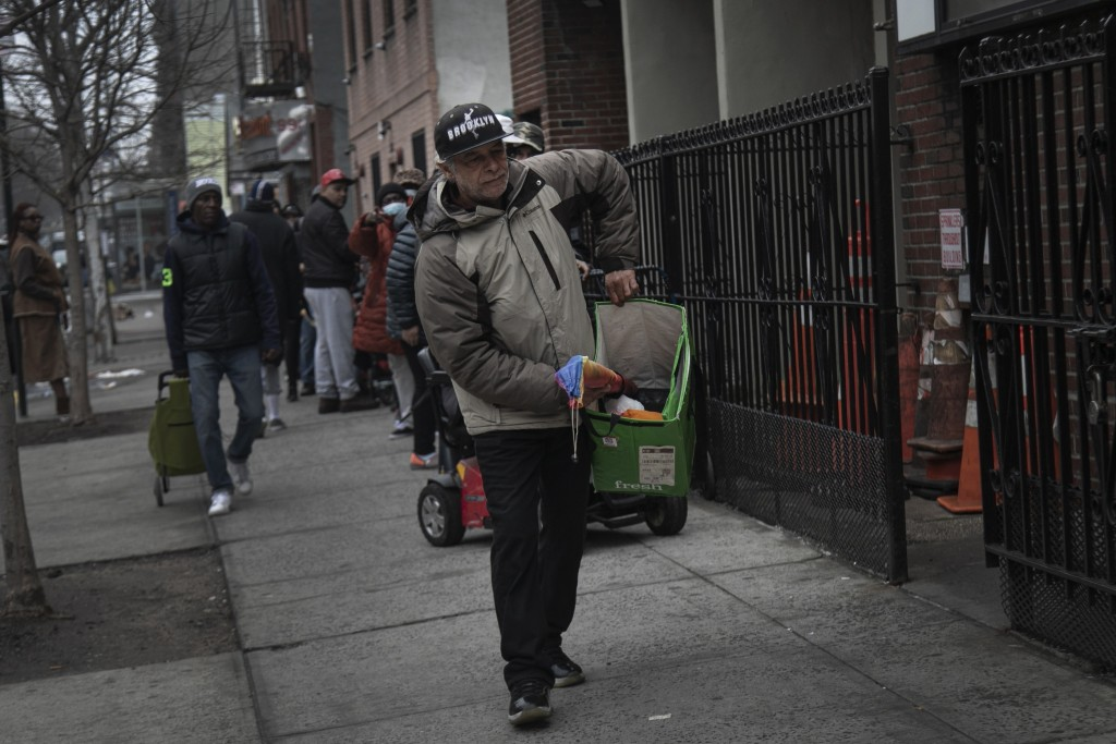 Jose Rosa, 63, moves forward in the queue where he waits to collect food donations from St. Stephen Outreach in the Brooklyn borough of New York, on F...