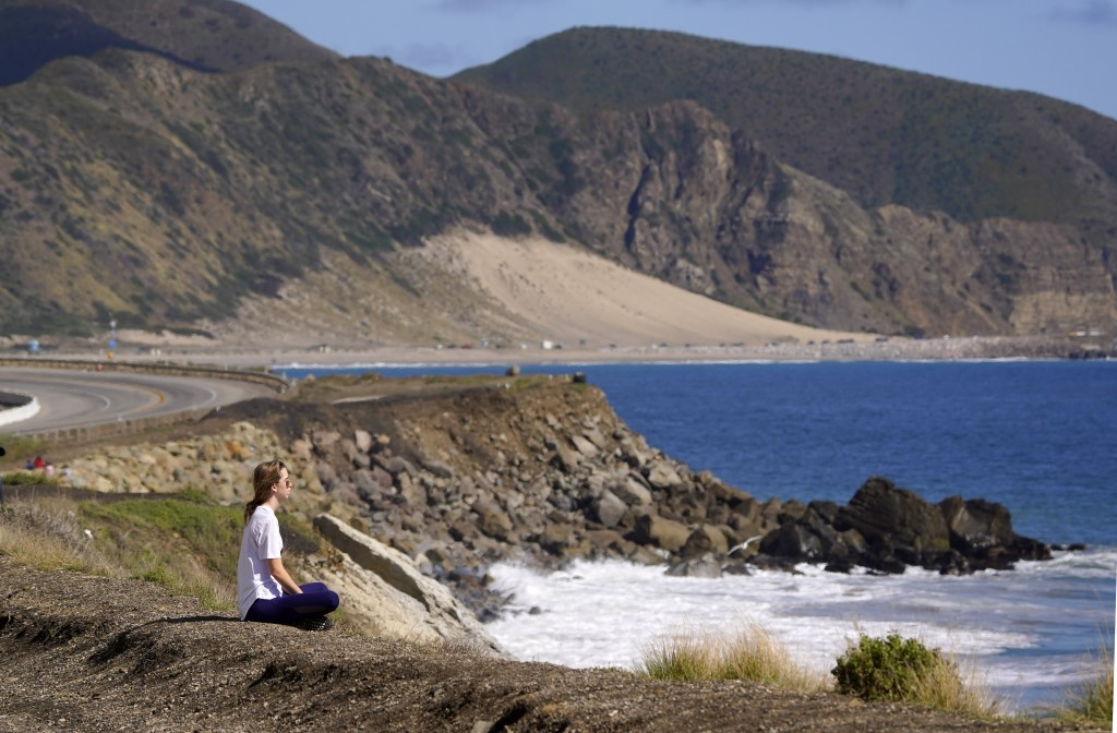 A woman sits alone in front of the ocean along Pacific Coast Highway, Monday, March 23, 2020, in Malibu, Calif. Officials are trying to dissuade peopl...
