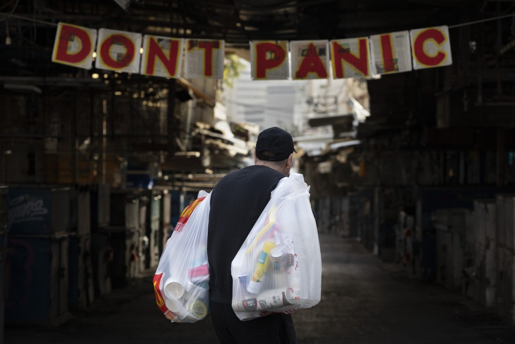 """A man carries his shopping as he walks by a """"don't panic"""" sign hanging at the entrance of a food market that is closed in order to reduce the spread o..."""