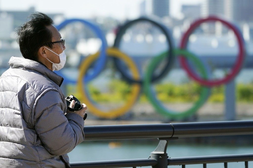 A visitor wearing a face mask stands near the Olympic rings at Tokyo's Odaiba district Tuesday, March 24, 2020. The Tokyo Olympics are probably going ...