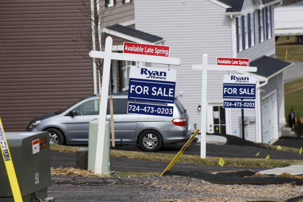 Model homes and for sale signs line the streets as construction continues at a housing plan in Zelienople, Pa., Wednesday, March 18, 2020.  U.S. new h...