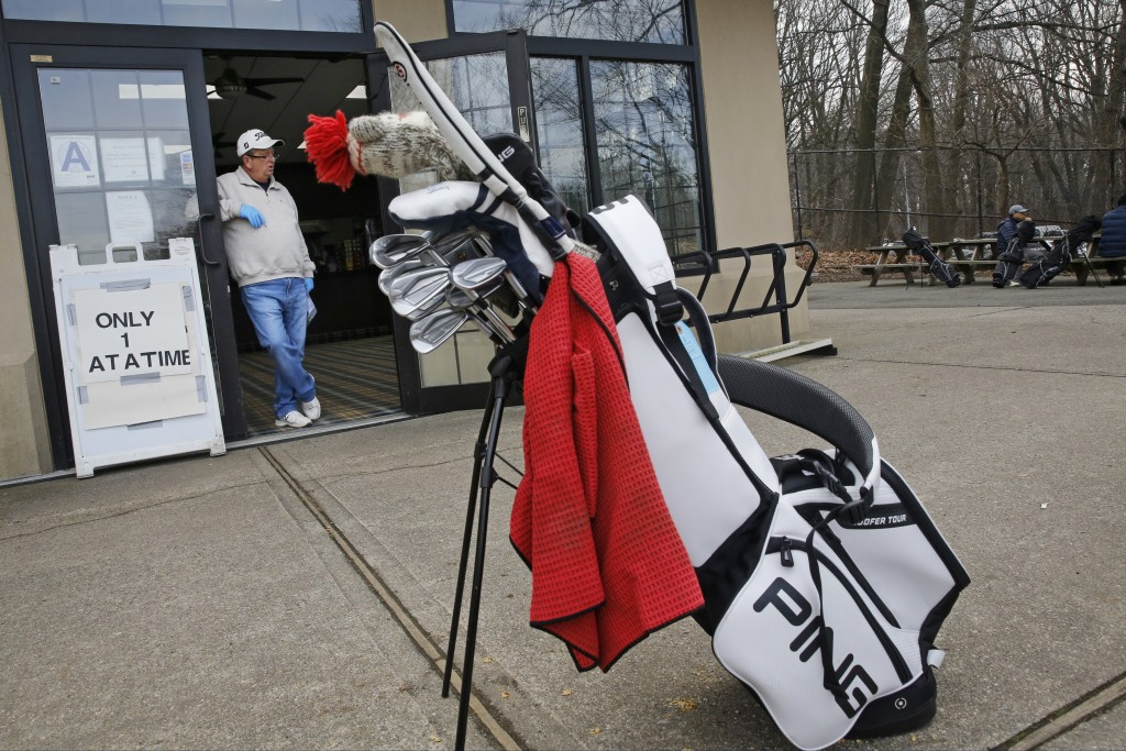 Employee Rick Lambert waits for golfers to arrive so he can stagger their tee times at the Forest Park Golf Course, Friday, March 20, 2020, in New Yor...