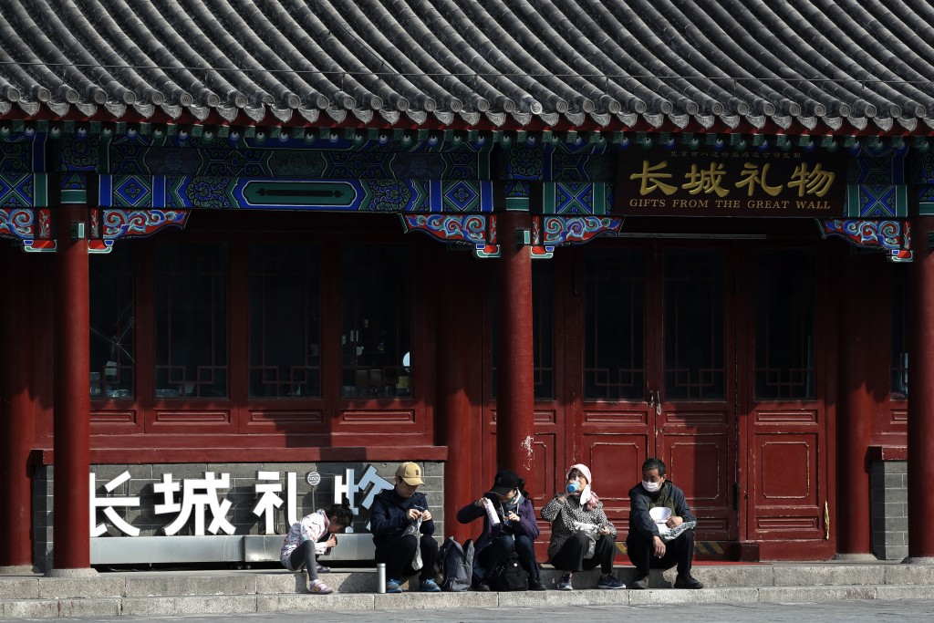 \Visitors wearing protective face masks take a rest outside a shuttered souvenir shop on the Badaling Great Wall of China after it reopened for busine...