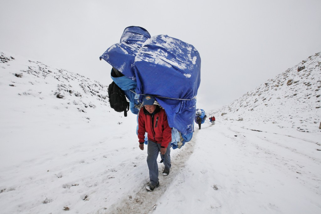 FILE - In this March 28, 2016, file photo, a porter walks with a massive load towards Everest Base camp near Lobuche, Nepal. The closure of Mount Ever...
