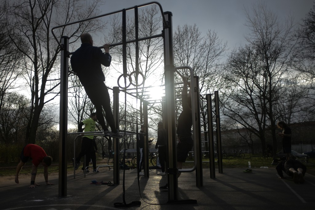 Men exercise at a free public gym at the Volkspark Friedrichshain in Berlin, Germany, March 19, 2020. (AP Photo/Markus Schreiber)