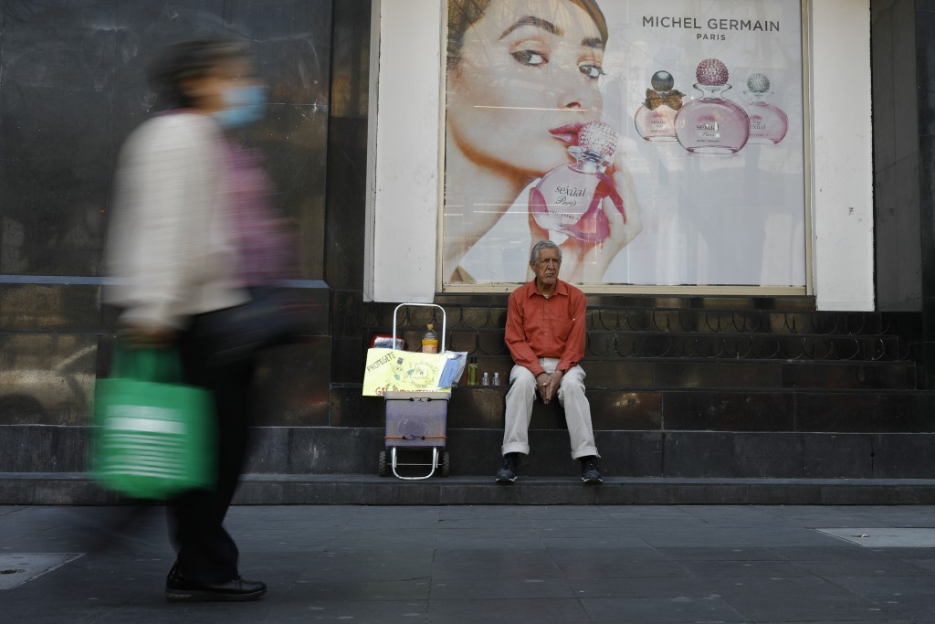 Tomas Gonzalez, 80, markets face masks and antibacterial gel to pedestrians in Mexico City, Monday, March 23, 2020. Gonzalez and his wife had been haw...