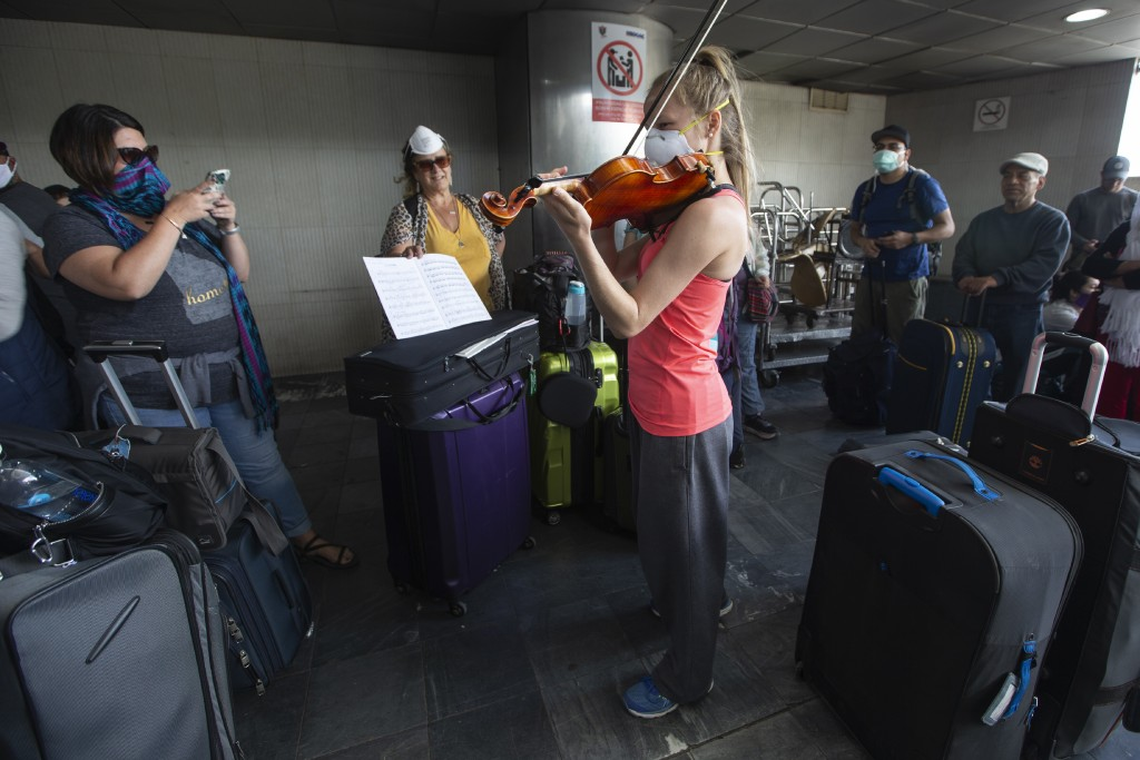 A traveler plays her violin prior to getting on a charter flight coordinated by the U.S. embassy at La Aurora airport in Guatemala City, Monday, March...