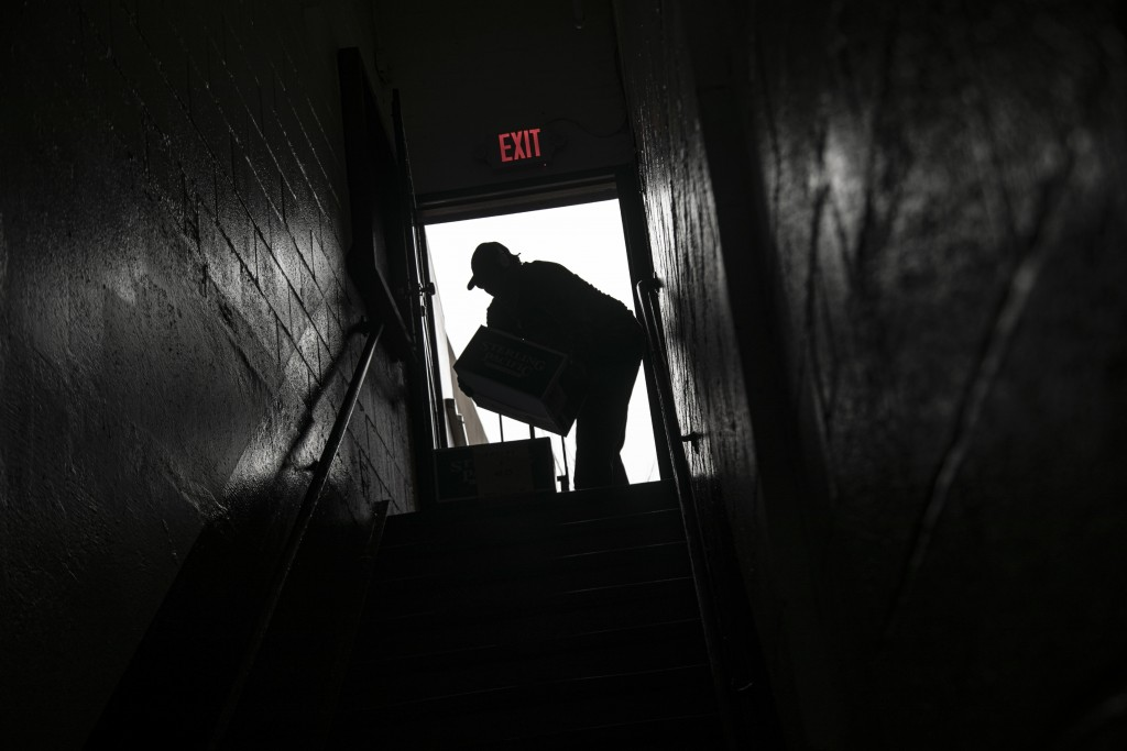 A volunteer is seen in silhouette as he carries cartons of food donations at St. Stephen Outreach in the Brooklyn borough of New York, on Friday, Marc...