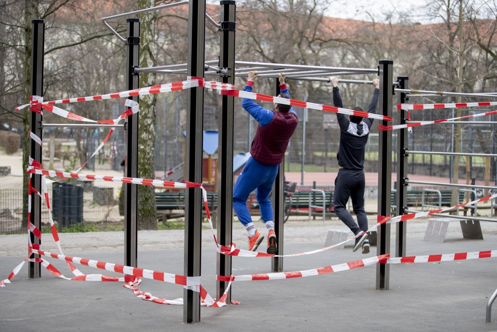 Two men exercise at a free public gym cordoned off with barrier tape in the Volkspark Wilmersdorf in Berlin, Germany, March 20, 2020. (Christoph Soede...