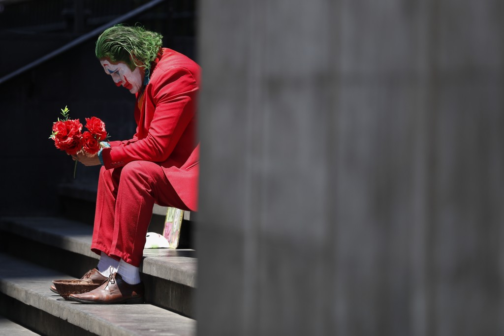 David Vazquez, a street performer dressed as the Joker, waits in hopes of pedestrians who will pay to take pictures with him in Mexico City, Monday, M...