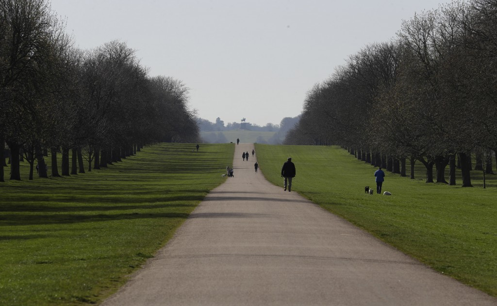 People keep a distance as they walk dogs on the Long Walk at Windsor Castle, England Tuesday, March 24, 2020. Britain's Prime Minister Boris Johnson o...