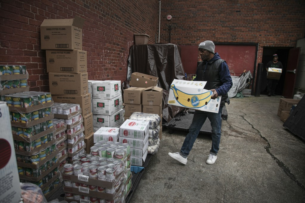 Rahim, a volunteer at the St. Stephen Outreach, carries food donations as he prepares to hand out food in the Brooklyn borough of New York, on Friday,...