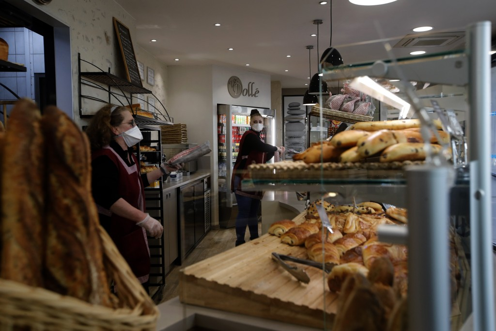 Bakers sell bread in a Boulogne Billancourt bakery, outside Paris, Tuesday, March 24, 2020. French President Emmanuel Macron urged employees to keep w...