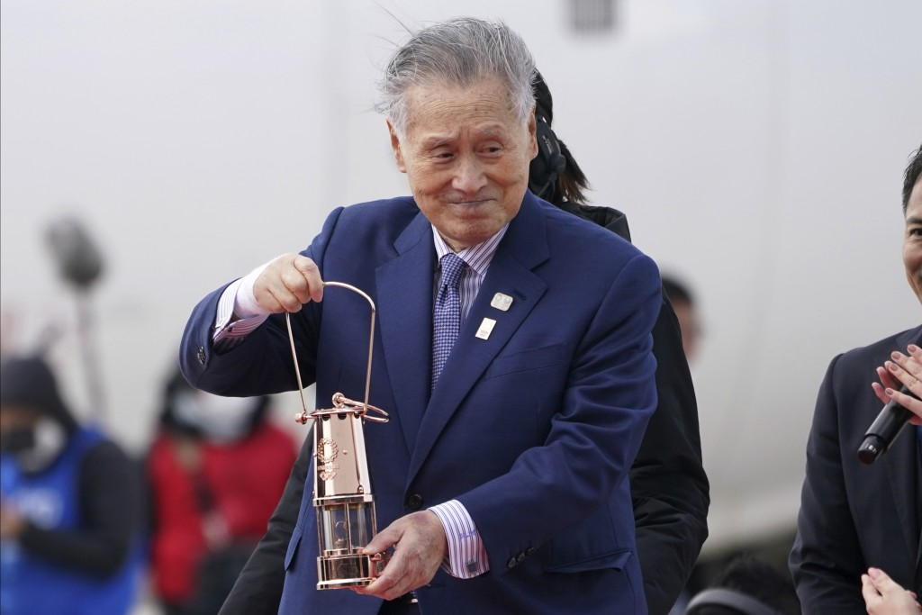 FILE - In this March 20, 2020, file photo, Tokyo 2020 Olympics chief Yoshiro Mori carries the Olympic flame during the Flame Arrival Ceremony at Japan...