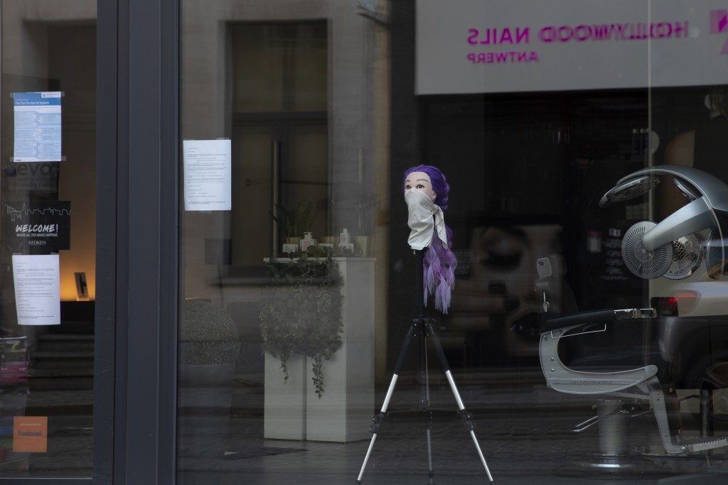 A mannequin head with a scarf around the nose and mouth is placed on a tripod in the window of a hairdressing salon in Antwerp, Belgium, Monday, March...
