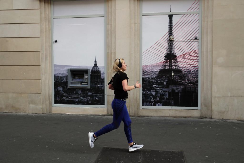 A woman jogs in Paris, March 22, 2020. (AP Photo/Francois Mori)