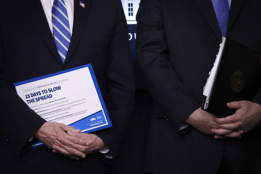 Vice President Mike Pence, left, and Attorney General William Barr hold binders as President Donald Trump speaks about the coronavirus in the James Br...