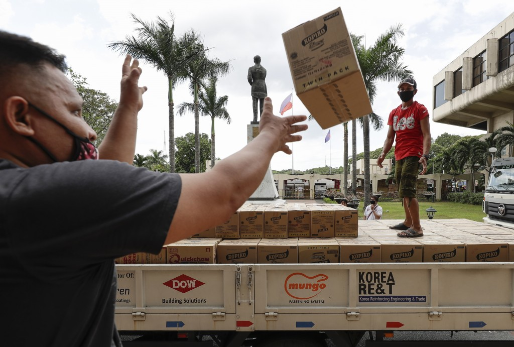 Volunteers and government workers unload boxes of canned food to be distributed to families following the enhanced community quarantine aimed to preve...