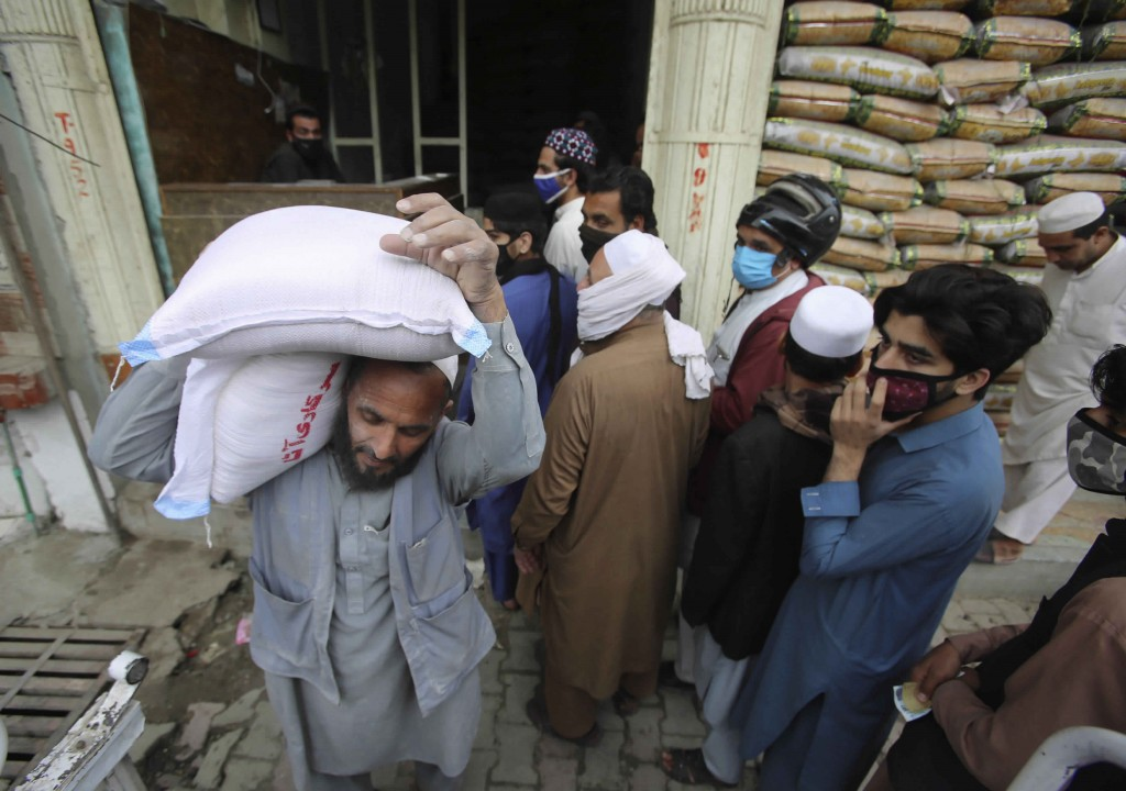 People buy sacks of flour fearing a shortage due to the coronavirus outbreak, in Peshawar, Pakistan, Tuesday, March 24, 2020. Pakistani authorities me...