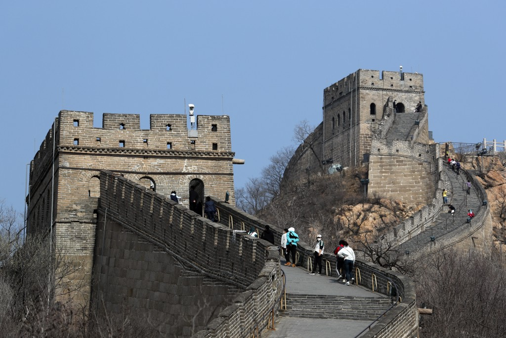Visitors wearing protective face masks walk on the Badaling Great Wall of China after it reopened for business following the new coronavirus outbreak ...