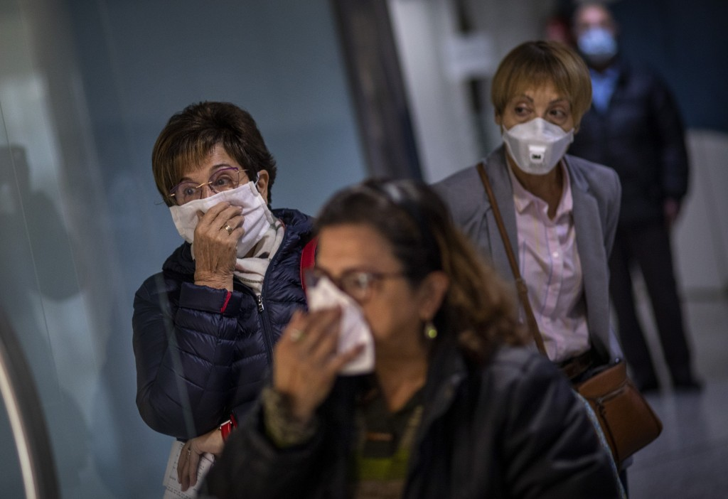 People wait their turn for a blood sample in a hallway of a hospital in Barcelona, Spain, March 18, 2020. Spain will mobilize 200 billion euros or the...