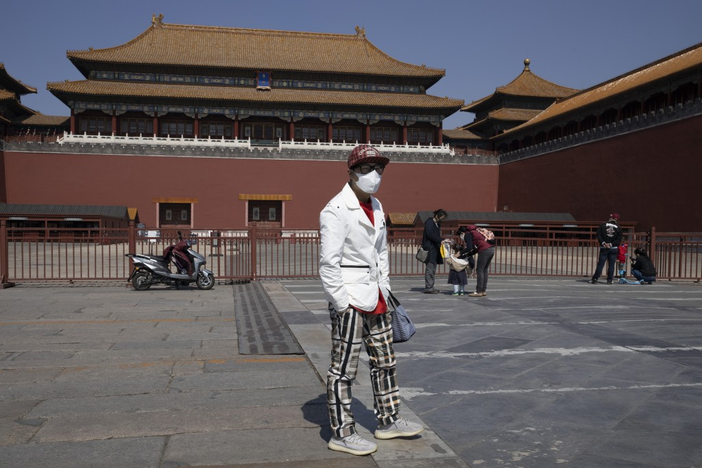 In this photo taken March 22, 2020, a visitor wears a face mask as he stands in front of the shuttered Forbidden City in Beijing, China. While many of...