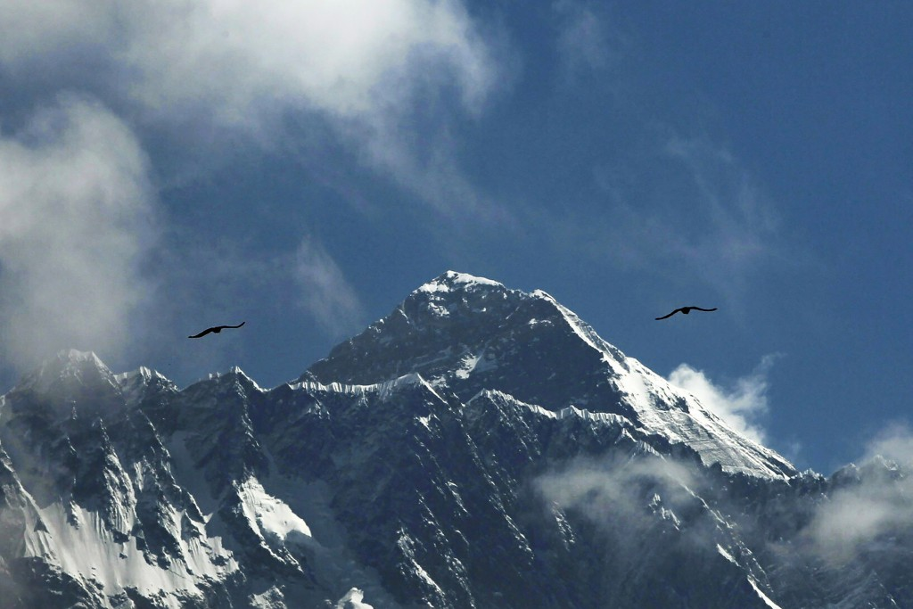 FILE - In this May 27, 2019, file photo, birds fly as Mount Everest is seen from Namche Bajar, Solukhumbu district, Nepal. The closure of Mount Everes...