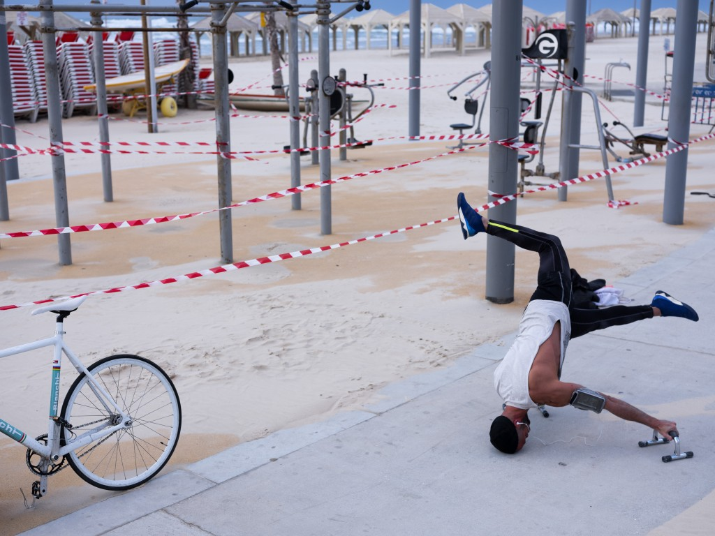 A free gym at Tel Aviv's beachfront is wrapped in tape to prevent public access as someone works out March 19, 2020. (AP Photo/Oded Balilty)