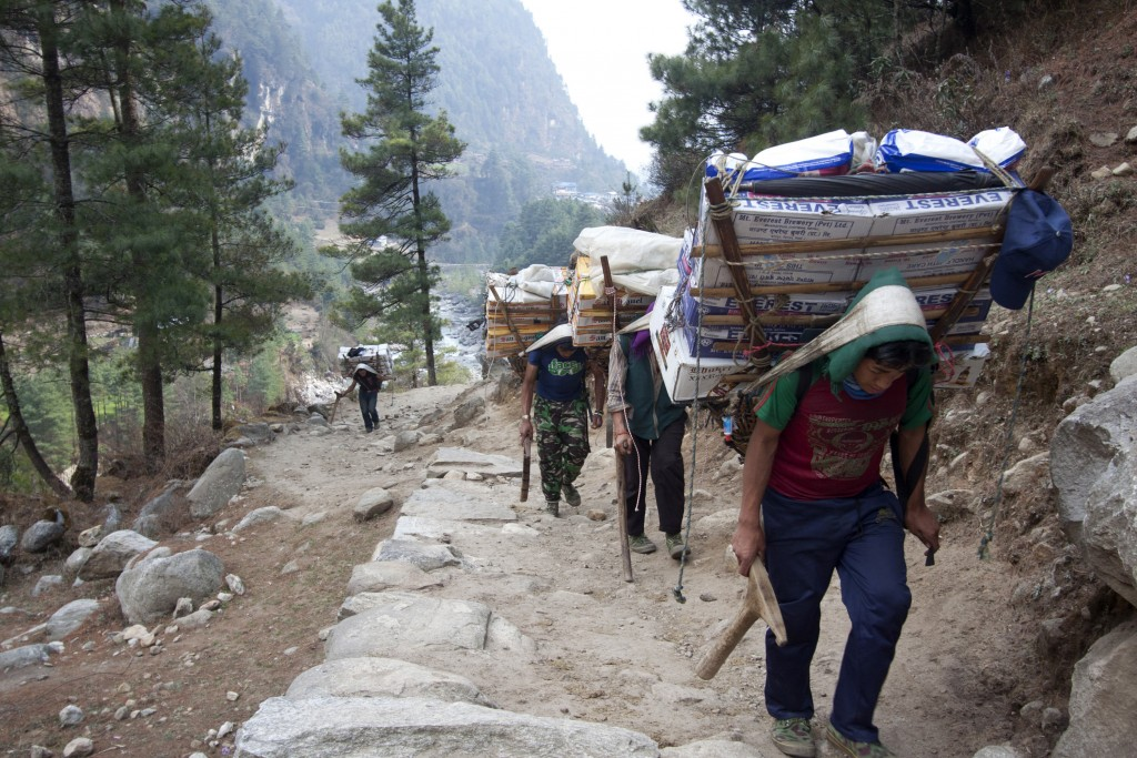 FILE - In this Tuesday, March 24, 2015, file photo, porters with supplies for trekkers head towards Namche, in Zamphute, a village in Nepal. The closu...