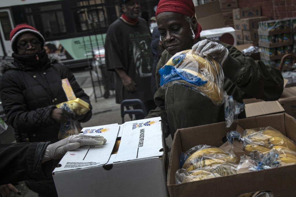 A volunteer gives out a bag of bananas at St. Stephen Outreach in the Brooklyn borough of New York, on Friday, March 20, 2020. For decades, American n...
