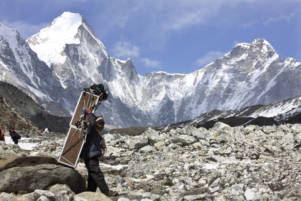 FILE - In this Friday, April 10, 2015, file photo, a porter carries crates containing oxygen tanks, with Mt Lingtren seen behind left, and Mt. Khumbut...